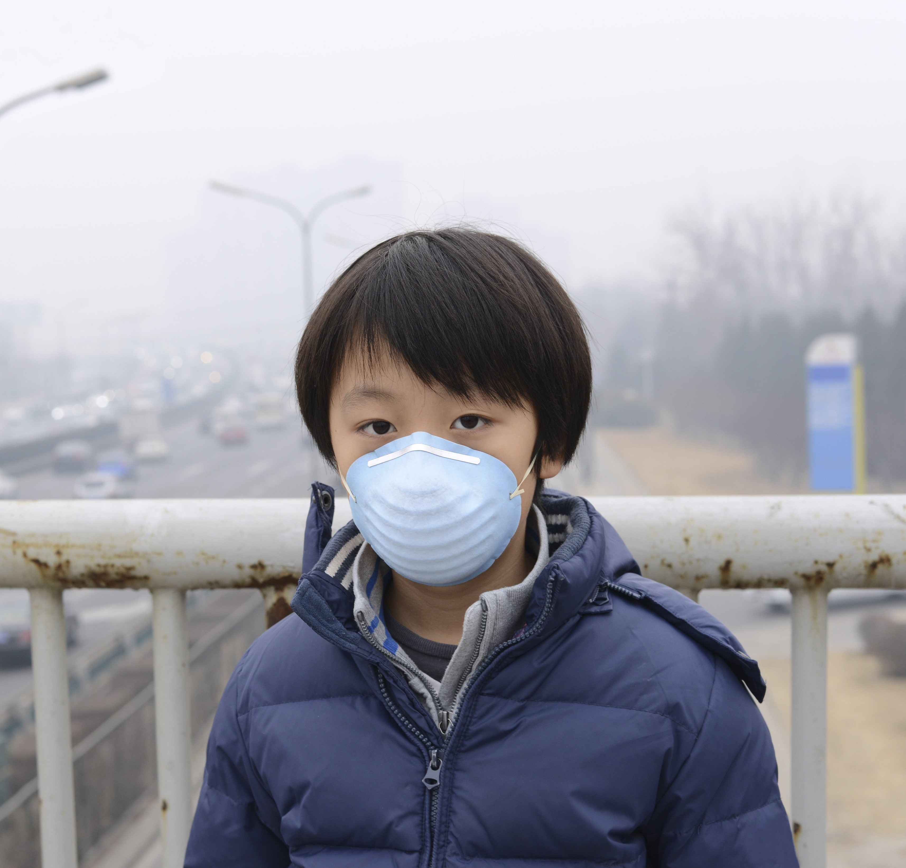 Boy wearing mask in China with polluted air behind