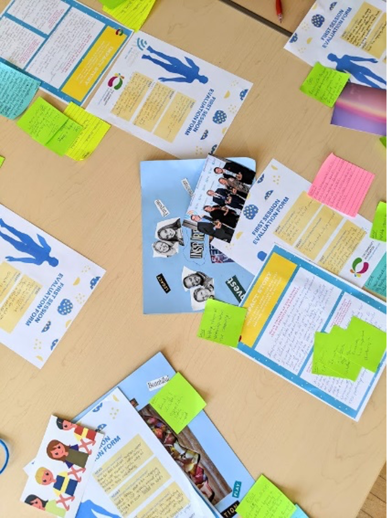 papers and pictures and sticky notes scattered across a table as in a workshop setting