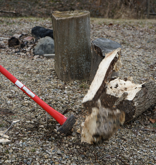 using an axe to chop firewood with wood pieces flying apart