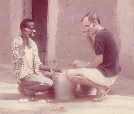 MQP and farmer Tchombiano Lamourdia checking eggs for freshness in Fada N'Gourma, Upper Volta, 1968, temperature 112 degrees Fahrenheit (44 Centigrade).