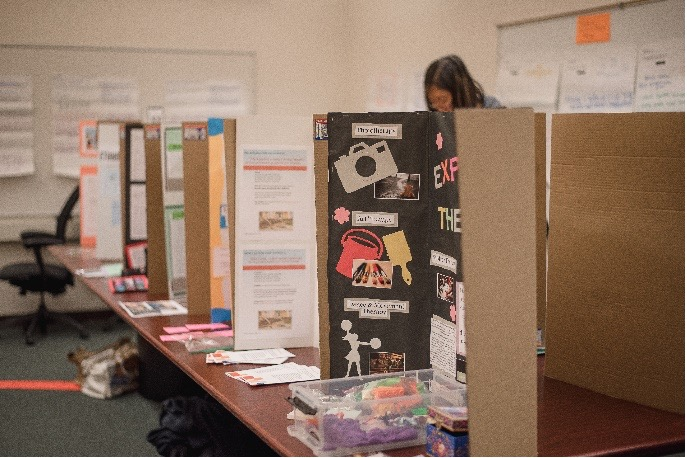 Image of classroom with trifold poster presentations and materials on tables and walls. Caption: Qualitative Research Celebration of Learning (Dec. 2019, Univ. of TN) Photo by Charaya Upton