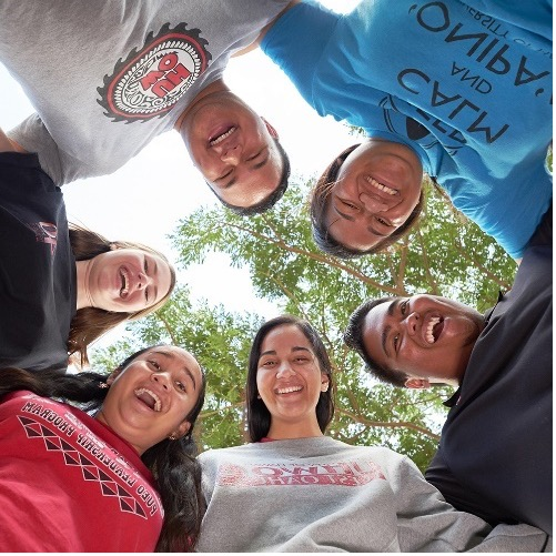 Image looking up at faces of 6 people standing arm in arm in a circle.