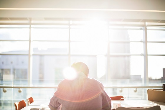 Person with back to camera sitting at desk with a bright sun flare