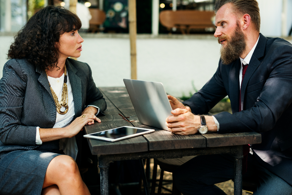 image of woman and man in work discussion and laptop computer